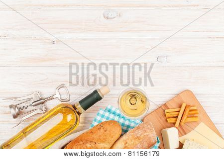 White wine, cheese and bread on white wooden table background with copy space
