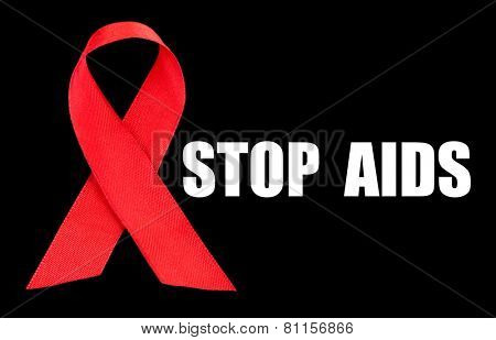 Red AIDS ribbon on black background