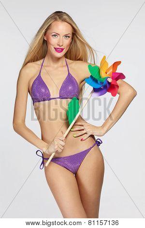 Female in lilac bikini with colorful windmill