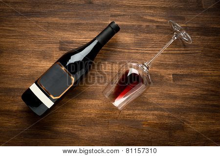 a bottle of wine and wine glass on old wood background.