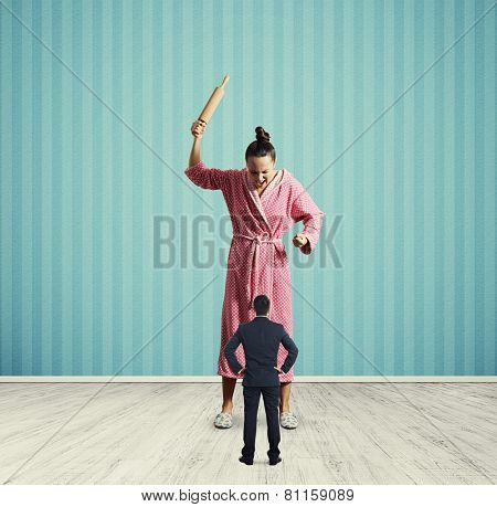 angry housewife screaming at small husband. photo in room with blue wall