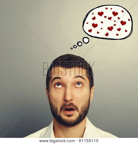 amazed young man looking up at speech bubble with red hearts. portrait over grey background