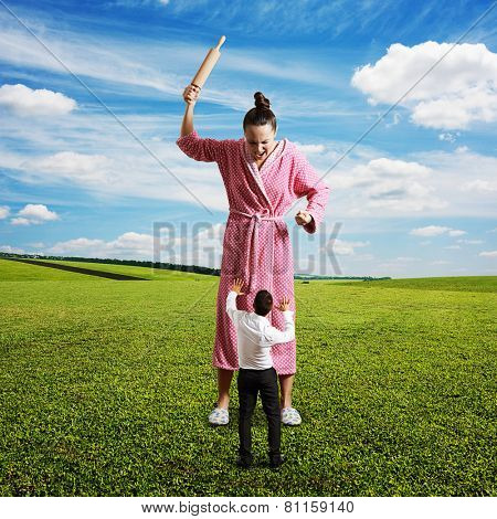 displeased housewife with rolling pin yelling at small startled husband. photo at outdoor