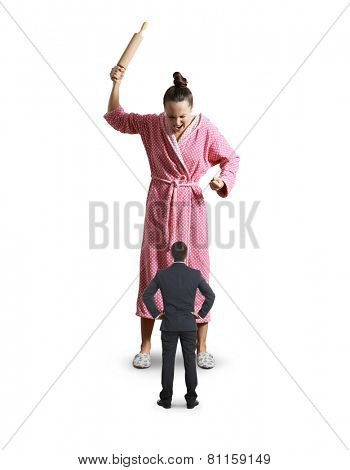 discontented housewife with rolling pin yelling at small husband. isolated on white background
