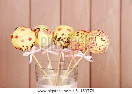 Tasty cake pops on wooden background
