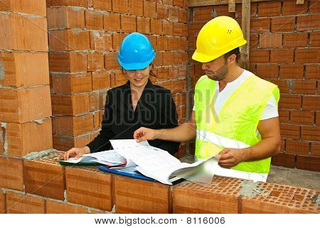 Constructions Workers Looking On House Plans