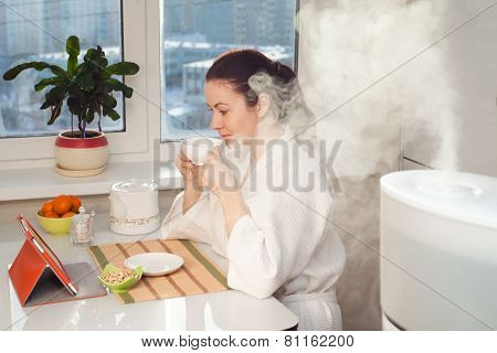 Woman Drinking Tea Reading Tablet At Humidifier