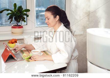 Woman Sitting With Tablet Pc On The Background Of Humidifier