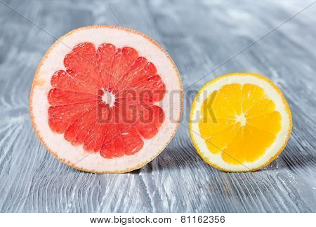 Slices Of Orange And Grapefruit. Close-up. Macro View. Gray Wood Background. Soft Focus.