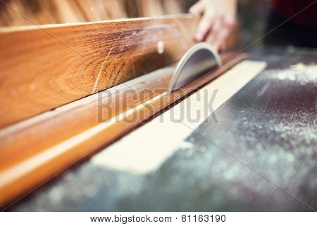 Carpenter sawing wooden planks