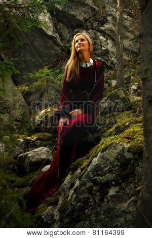 beautiful woman fairy with long blonde hair in a historical gown is sitting amids moos covered rock