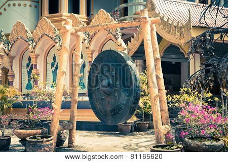 Large gong in the temple and in the background the typical architecture Thailand Asia.