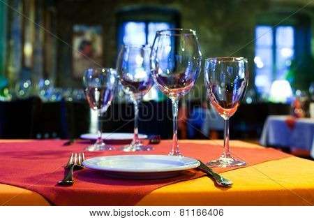 Restaurant Hall. Table With Red And Orange Tablecloth, Wine Glasses, White Plates And Cutlery. (soft