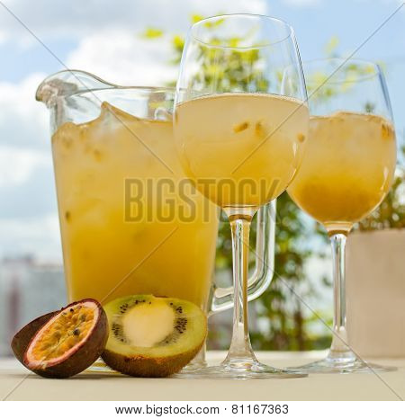 Maracuya And Kiwi Lemonade Pitcher With Two Glasses On The Table. Sky Background. Sliced Kiwi And Pa