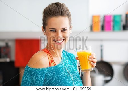 Portrait Of Smiling Fitness Young Woman With Glass Of Pumpkin Smoothie
