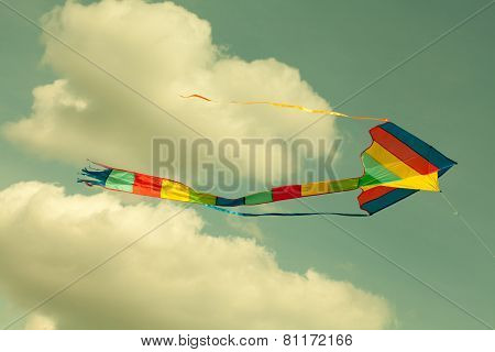 Multicolor Kite Flying In The Cloudy Sky. Retro Style. (toned Photo.)