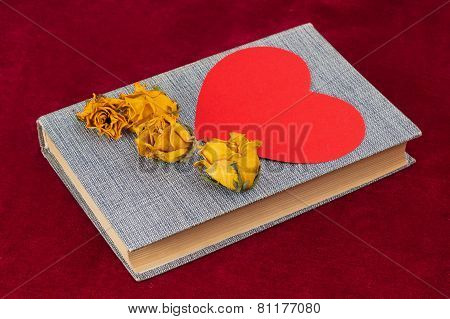 Four Dried Yellow Roses And Red Paper Heart Lying On The Book