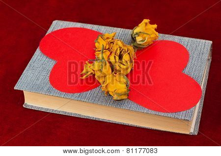 Five Yellow Roses And Two Red Paper Hearts Lying On The Book