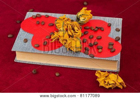 Five Roses And Two Hearts Lying On The Book With Coffee Beans