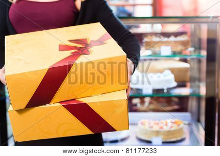 Woman presenting cake and pastries in takeaway boxes in cafe or pastry shop