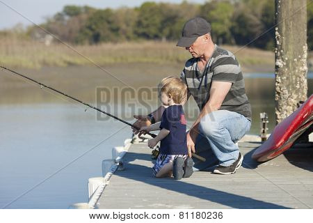 father and son fishing on dock, father gives instruction