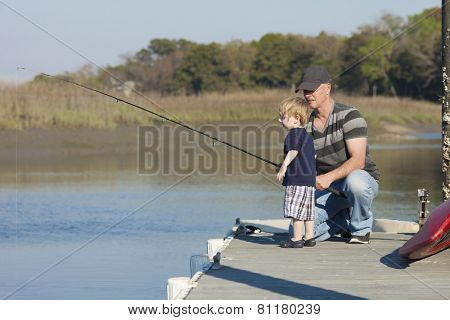 father giving fishing instructions to young son or grandson
