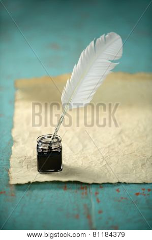 Inkwell and feather with old paper on grunge table