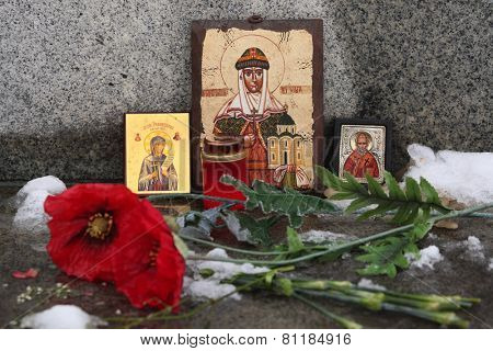 Russian orthodox icons of Saint Olga and Saint Nicholas and poppy flowers at a cemetery.