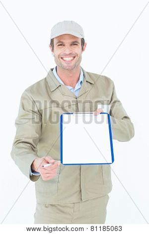 Portrait of happy delivery man giving clipboard and pen for signature over white background
