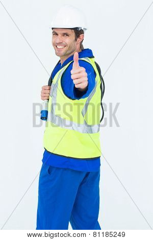 Side view portrait of happy man showing thumbs up sign over white background