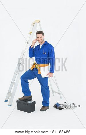 Portrait of smiling repairman with toolbox and ladder using cellphone against white background