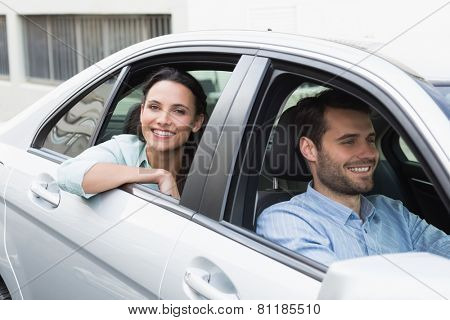 Young couple smiling at the camera in their car