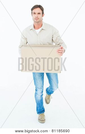 Delivery man carrying cardboard box while walking against white background