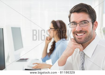 Portrait of a smiling businessman with glasses in the office