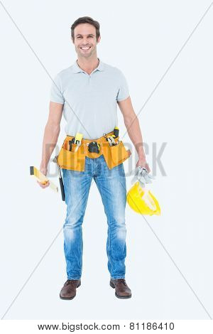 Portrait of happy repairman holding spirit level and hardhat over white background