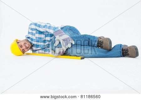 Full length of construction worker suffering from knee pain while lying against white background