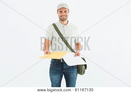 Portrait of happy courier man giving envelops on white background