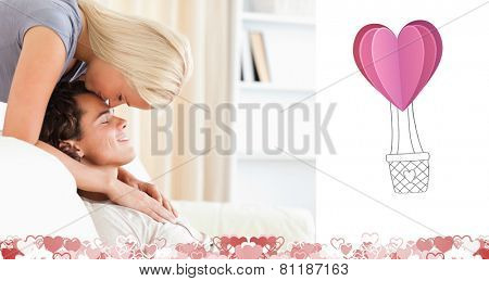 Woman kissing her fiance on the forehead against heart hot air balloon