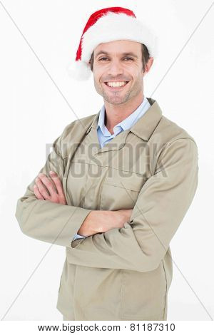 Portrait of happy delivery man in Santa hat standing arms crossed against white background