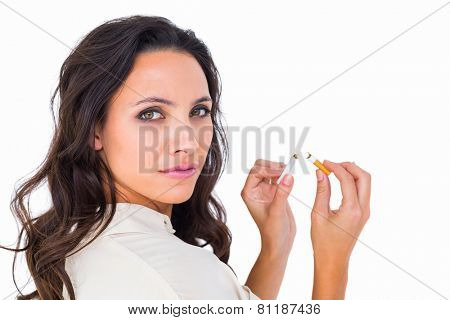 Pretty brunette snapping a cigarette on white background