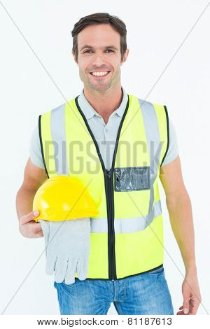 Portrait of confident construction worker holding gloves and hardhat over white background