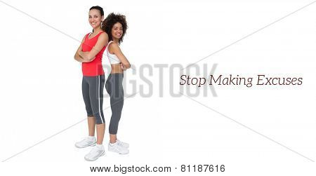 Portrait of two fit young women standing with arms crossed over white background