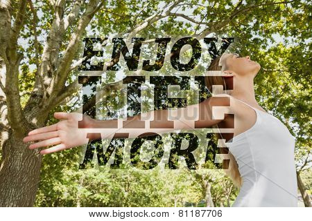 Content young woman doing yoga in a park against enjoy life more