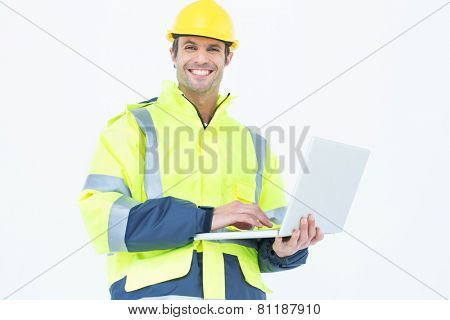 Portrait of male architect in reflective clothing using laptop over white background