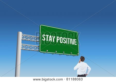 The word stay positive and thinking businessman touching his chin against blue sky