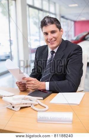 Smiling salesperson holding a document at new car showroom