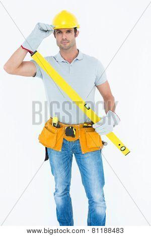 Portrait of confident carpenter holding spirit level while wearing hard hat over white background