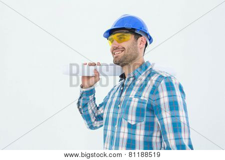 Smiling architect looking away while holding blueprint against white background