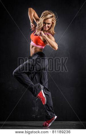 Fitness dancer girl in passionate pose on gray background