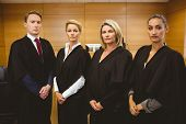 picture of court room  - Four serious judges standing while wearing robes in the court room - JPG